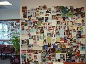 Fertility Success with Dr. Lee with acupuncture and herbal treatments. front of reception wall filled with baby photos.
